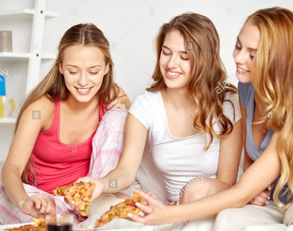 happy-friends-or-teen-girls-eating-pizza-at-home-FXW5J3